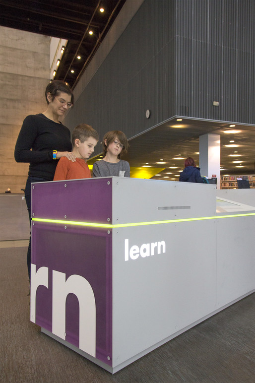 Visitors interact with touch station.