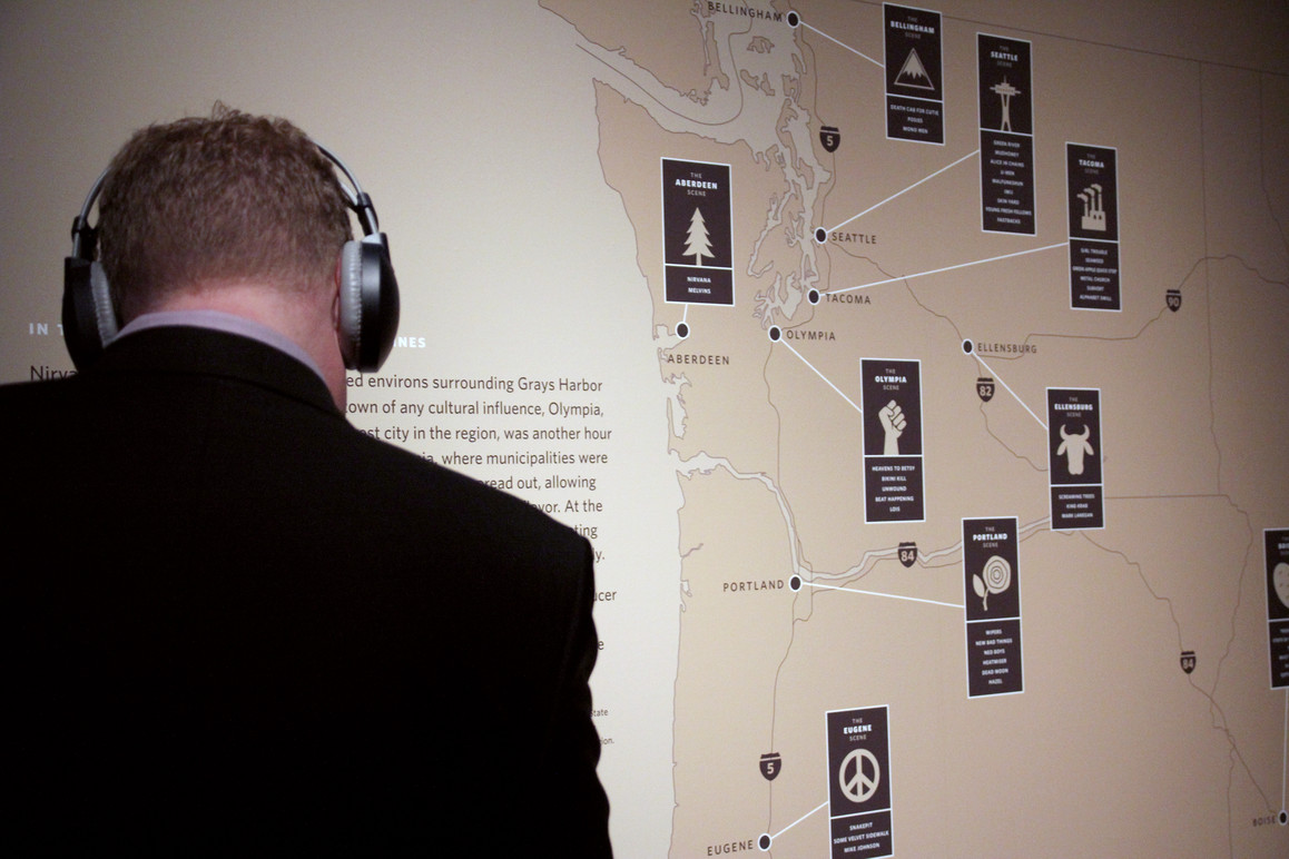"A visitor listening to the bands represented in the ""Micro scenes"" of the pacific northwest infographic."
