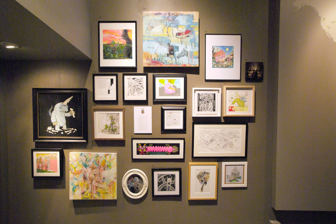 Wall of framed artwork.