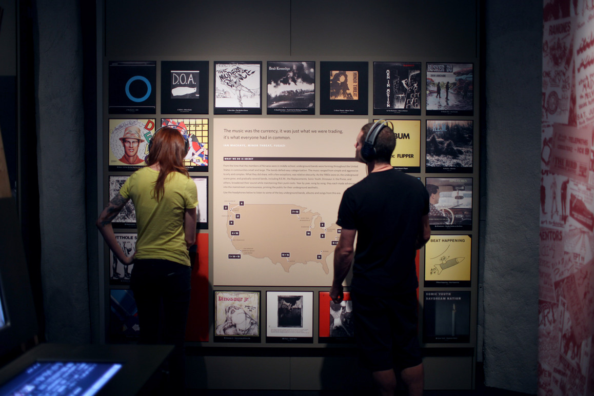 Visitors looking at album artwork and listening at one of the record walls.