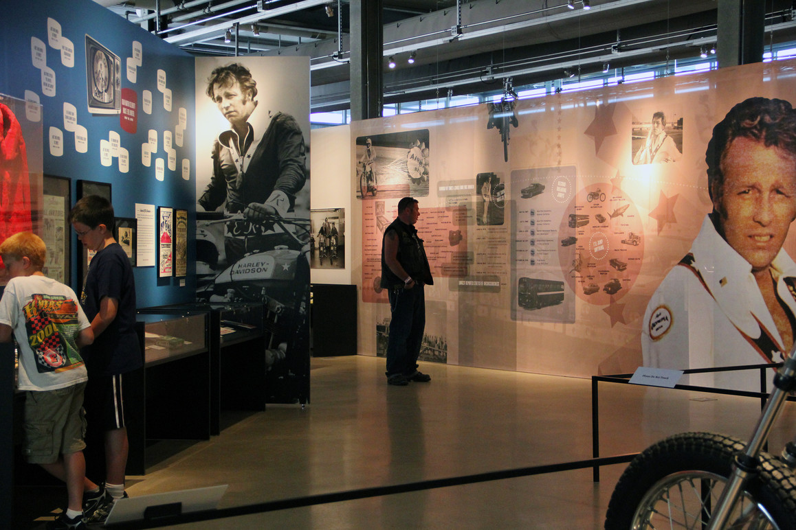 Visitors looking at the artifacts and the infographic listing all of Evel's television appearances.